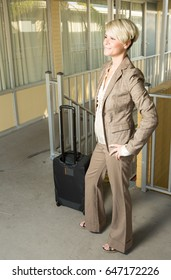 Young attractive businesswoman dressed in a pantsuit in a motel courtyard with her bag