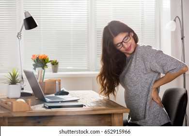 Young Attractive Businesswoman Having Back Pain In Office