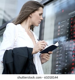 Young attractive businesswoman making notes while looking on the currency display