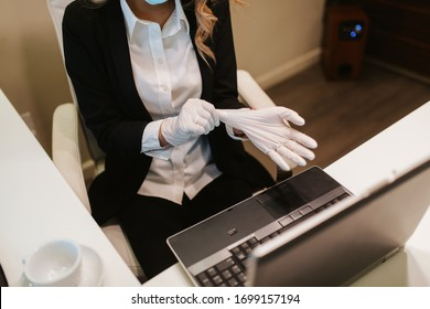 Young attractive businesswoman with mask and gloves in office. COVID - 19 virus protection