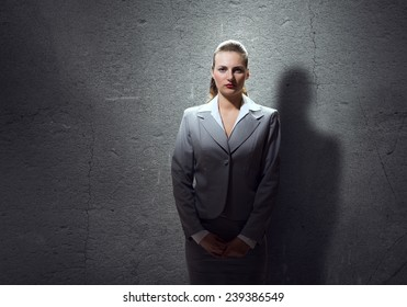 Young attractive businesswoman in room against cement wall