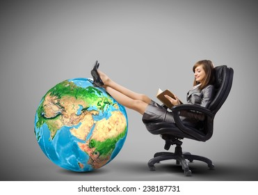 Young attractive businesswoman sitting in chair and reading book. Elements of this image are furnished by NASA