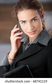 Young attractive businesswoman smiling happily, talking on mobile phone.?