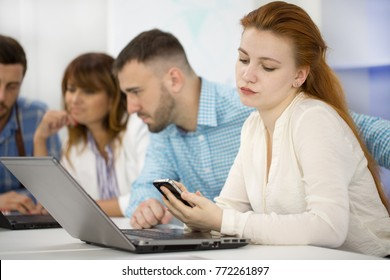 Young attractive businesswoman using her smart phone during business meeting with colleagues at the office copyspace communication carrier cell mobility distracting distraction concept