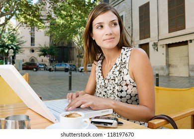 Young attractive businesswoman using a laptop computer and smiling while sitting at a coffee shop terrace in a classic city, outdoors.