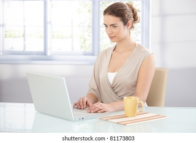 Young attractive businesswoman working in bright office, using laptop.?