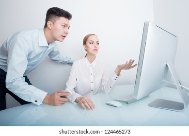 Young attractive businesswomen and businessman looking at the computer