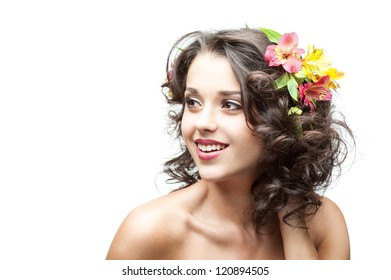 young attractive caucasian brunette girl with red and yellow flowers in hair which looking away and gently smiling