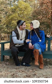 Young attractive caucasian couple in love sitting on a bench in the park in autumn or winter while the man proposes marriage to the woman