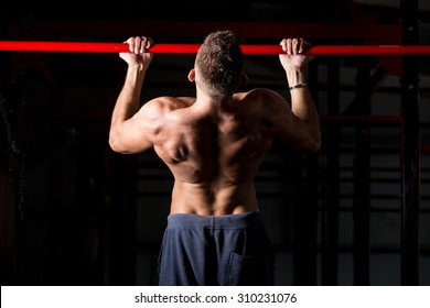 Young attractive caucasian crossfit sportsman working out in gym, exercising on chin-up bar, doing pull-ups for arms and back muscles, rear view