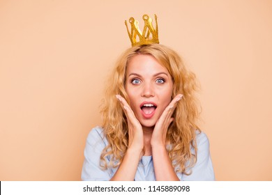 Young attractive caucasian curly-haired gorgeous cheerful sweet smiling happy amazed woman wearing golden crown and blue dress. Isolated over pastel yellow background
