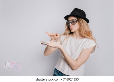 Young attractive Caucasian girl in glasses and a hat scatters Euro banknotes on a white background. Easy to part with money.
