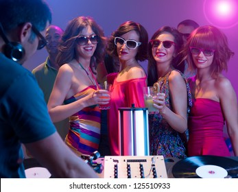 young attractive caucasian girls dancing and having fun at a party with sunglasses and cocktails in their hands in front of a dj mixing music with turntables