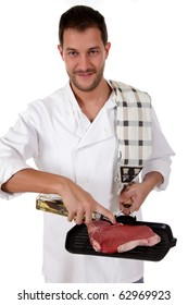 Young attractive caucasian male cook with uniform preparing a tender t-bone steak for grill. Studio shot. White background.
