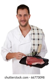 Young attractive caucasian male cook with white uniform carrying a grill with a tender t-bone steak. Studio shot. White background.
