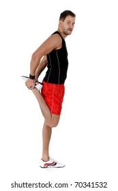 Young attractive caucasian man athlete doing fitness exercises, flexed leg. White background. Studio shot.