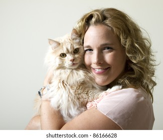 A young, attractive caucasian woman holding a long haired blonde cat.