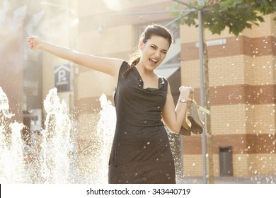 Young attractive cheerful woman walking in city, summer hot outdoor near fountain.