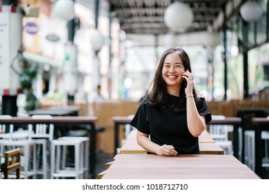 A young and attractive Chinese Asian woman is smiling while she's talking on her smartphone in a city in Asia. It is a portrait of her against a blurred background. She looks happy and delighted.