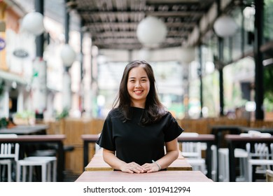 A young and attractive Chinese Asian woman is smiling while she leans on a table in a restaurant in a city in Asia during the day. She is dressed in smart casual and is relaxed and happy.