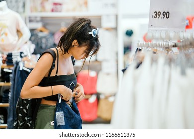A young and attractive Chinese Asian woman browses the shelves at a store for clothing to buy. The millennial teenager is wearing trendy street clothes and is smiling as she looks through the store.