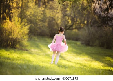 Young attractive classic dance performer workout at the spring garden. 9 years girl runs in the magic evening sunlight in pink ballet dress. Active and healthy kid have fun outdoor in park