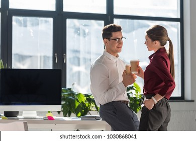 young attractive colleagues with paper cups of coffee talking and flirting at office