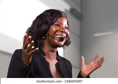 young attractive and confident black African American business woman with headset speaking in auditorium at corporate training event or seminar giving motivation and success coaching conference
