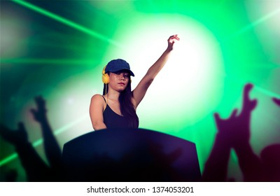 young attractive and cool Asian Chinese DJ woman with headphones at night club remixing techno music with lights background in clubbing fun and deejay lifestyle concept