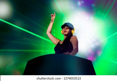 young attractive and cool Asian Japanese DJ woman with headphones at night club remixing techno music with lights background in clubbing fun and Deejay lifestyle concept