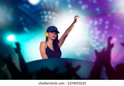 young attractive and cool Asian Korean DJ woman with headphones at night club remixing techno music with lights background in clubbing fun and deejay lifestyle concept