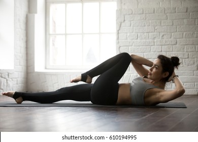 Young attractive cool sporty woman doing crisscross fitness exercise, bicycle crunches, working out on the floor, wearing black sportswear bra and black pants, full length white loft studio background