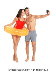 Young attractive couple in beachwear with inflatable ring taking selfie on white background