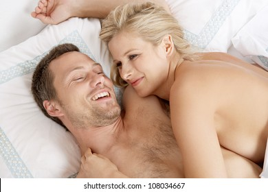 Young attractive couple being playful in bed.
