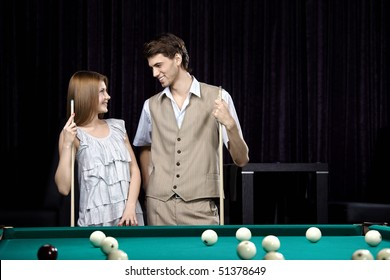 Young attractive couple at a billiard table