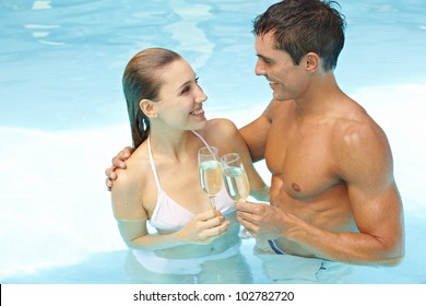 Young attractive couple with champagne in swimming pool