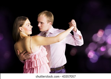 Young attractive couple dancing. Space for text.