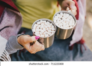 Young attractive couple drinking cocoa with marshmallows in a forest
