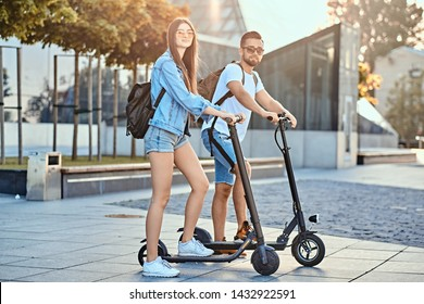 Young attractive couple is enjoying nice summer day while riding their own electro scooters.