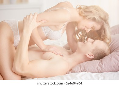 Young attractive couple enjoying sensual romantic foreplay in bed
