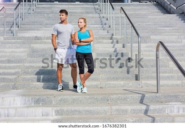Young attractive couple exercising in stairs after training