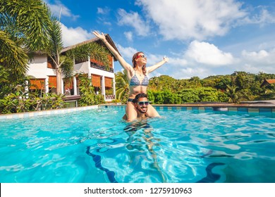 Young attractive couple having fun in the outdoor pool, the girl sits on the shoulders of the guy, luxury  vacation, real estate in the tropics, honeymoon