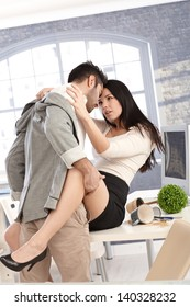 Young attractive couple having sex in office, kissing and embracing.