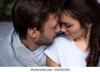 Young attractive couple hugging in bedroom