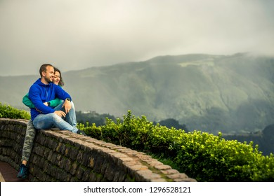 Young and attractive couple is hugging and sitting on the edge of view point on Azores Islands. Clouds and mountains on background. Portugal.