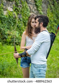 Young attractive couple learns how to shoot from the bow