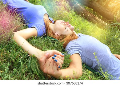young attractive couple in love, hand in hand, lying on the green grass in a park closing eyes and dreaming. concept of true love tenderness and future hopes. sunburst and lens flare effects added.