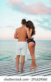 Young attractive couple in love, Handsome man and sexy woman with perfect tan slim fit body enjoying romantic evening on the beach, Holding hands watching on the sea.