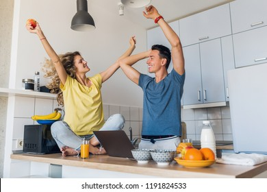 young attractive couple of man and woman cooking breakfast together in morning at kitchen, happy family, romantic, healthy food, freelancer at work on laptop, dancing to music, having fun, laughing