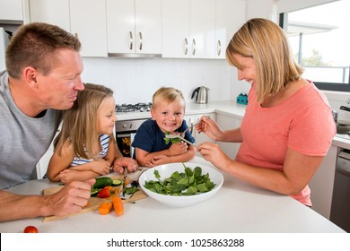 young attractive couple mother and father preparing salad together with little son and young beautiful daughter in healthy vegetable nutrition education and family lifestyle concept
